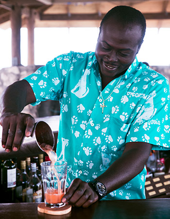 man happily mixes a tropical drink